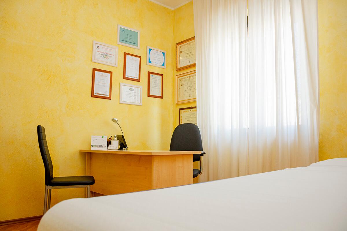 immagine studio colore giallo antonio daniele osteopata scrivania attestati e lettino massaggi